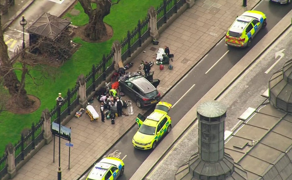 """In this image taken from video, police officers gather around a car adjacent to Houses of Parliament in London. Five people were killed, including the assailant, and 40 others were injured in what Prime Minister Theresa May condemned as a """"sick and depraved terrorist attack."""" AP"""