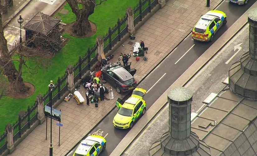 In this image taken from video police officers gather around a car adjacent to the Houses of Parliament on Wednesday. AP