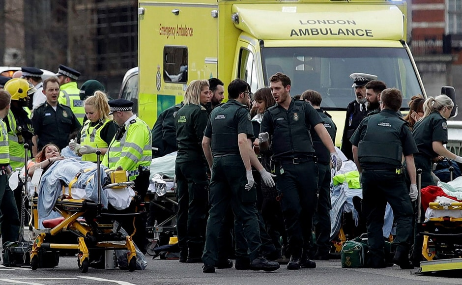 Emergency services staff provide medical attention close to the Houses of Parliament in London. Lawmakers, lords, staff and visitors were locked down after the assailant was shot by police within the perimeter of Parliament. AP