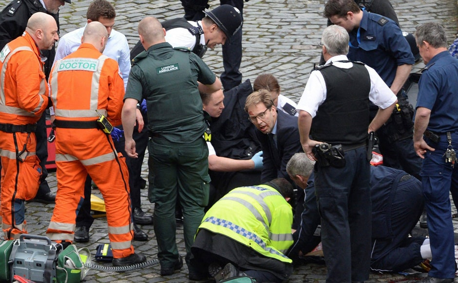 """Conservative Member of Parliament Tobias Ellwood (centre) helps emergency services attend to an injured person outside the Houses of Parliament, London. A doctor who treated the wounded from the bridge said some had """"catastrophic"""" injuries. AP"""