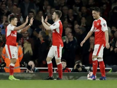 Arsenal's Aaron Ramsey, centre, is congratulated by Alexis Sanchez after scoring against Lincoln City. AP