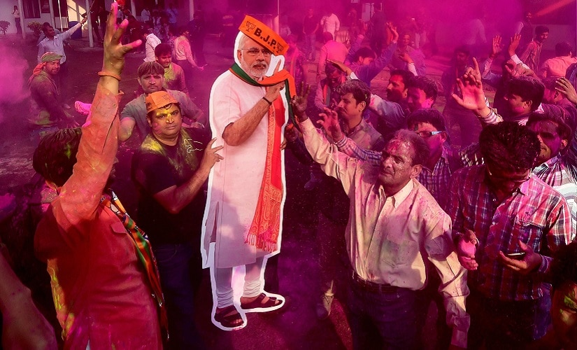 New Delhi: BJP workers play holi with a giant cut-out of Prime Minister Narendra Modi as they celebrate the party's victory in the UP and Uttarakhand Assembly elections, at the party headquarters in New Delhi on Saturday. PTI Photo by Manvender Vashist(PTI3_11_2017_000219B)