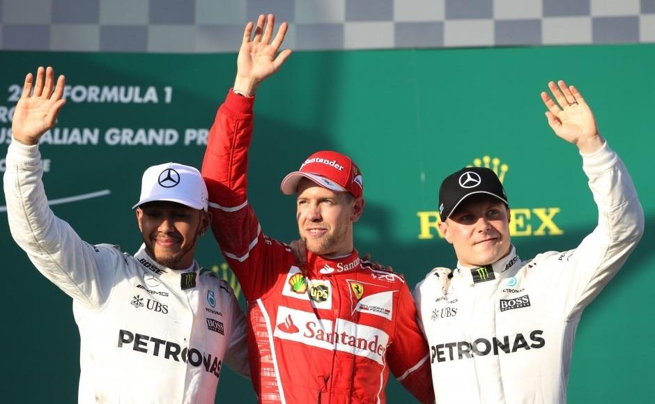 Sebastian Vettel of Ferrari celebrates his win on the podium with second placed Lewis Hamilton of Mercedes GP and teammate Valtteri Bottas at the Australian Formula One Grand Prix at Albert Park. Getty