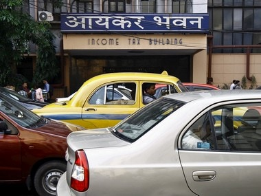 Commuters sit in cars in front of the income tax building during a traffic jam in Kolkata April 2, 2015. U.S. and European investor groups have called for the Indian government to urgently clarify its tax regime for foreigners, following surprise attempts by tax inspectors to claw back money they say is owed on years of previously untaxed gains. REUTERS/Rupak De Chowdhuri - RTR4VVMQ