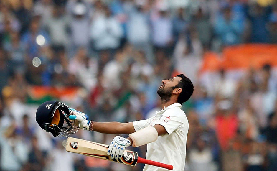 India's Cheteshwar Pujara looks skywards as he raises his bat and helmet to celebrate a crucial centuryon the fourth day against Australia. AP