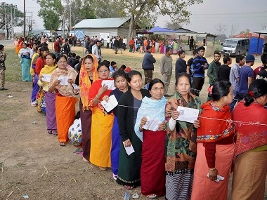 Voters stand in queues at a polling booth in Manipur. PTI