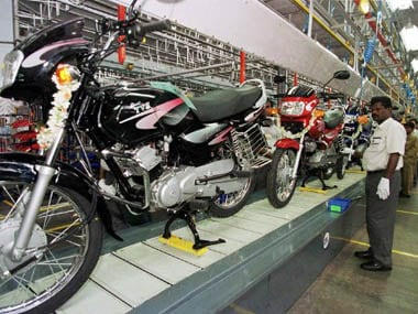 "A worker keeps a close eye on the first lot of ""TVS Victor"" motorbikes as they roll off the company's production unit at Hosur in Tamil Nadu state 12 July 2001. The TVS Victor is the first indigneously built four-stroke, 110cc motorbike from the TVS stable. (FILM) AFP PHOTO/INDRANIL MUKHERJEE"