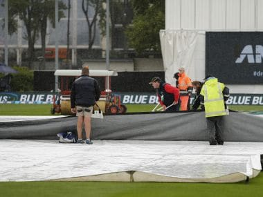 Ground staff clear water from the covers as rain delays play on the final day of the first Test between South Africa and New Zealand. AP