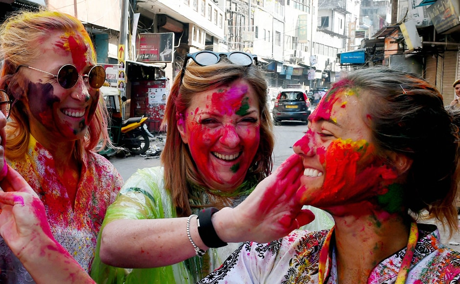 Foreigners playing with colours on the occasion of ' Holi festival' celebration in New Delhi on Monday. PTI