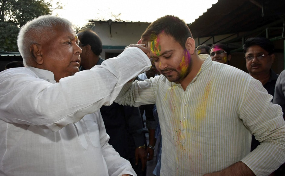 Patna: RJD Chief Lalu Prasad with his son and Bihar deputy CM Tejashwi Yadav during Holi celebrations in Patna on Monday. PTI