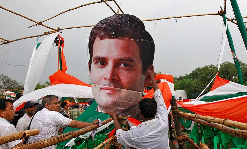 A worker from Congress party holds a broken cut-out of Rahul Gandhi. Reuters