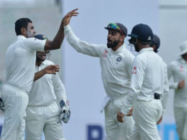 The Indian team celebrates the dismissal of David Warner on Day 2 of the second Test between India and Australia in Bengaluru. AFP