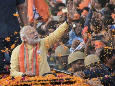 Prime Minister Narendra Modi waves to people during his road show in Varanasi