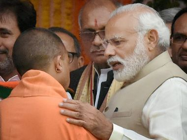 Prime Minister Narendra Modi speaks with UP chief minister Yogi Adityanath after the swearing-in ceremony in Lucknow. PTI