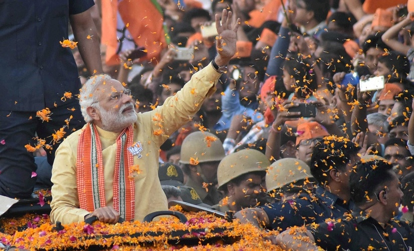 Prime Minister Narendra Modi waves to people during his road show in Varanasi on Sunday. PTI