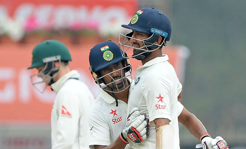 India's Cheteshwar Pujara is congratulated by Wriddhiman Saha after completing 150 runs in the Ranchi Test against Australia. AFP