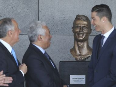 Portuguese president Marcelo Rebelo de Sousa, left, Portuguese PM Antonio Costa, 2nd left and Real Madrid's Cristiano Ronaldo stand next to a bust of the player at the Madeira Airport. AP Photo