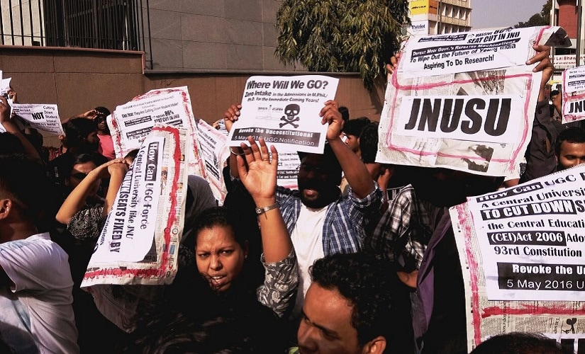 JNU students protesting massive seat cut in MPhil and PhD courses on Friday staged a protest outside the UGC building. News18