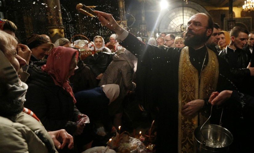 An Orthodox priest blesses traditional Easter cakes and painted eggs prepared for Easter celebrations in the Kyiv-Pechersk Lavra church, also known as the Kiev Monastery of the Caves, in Kiev, Ukraine, Sunday, April 16, 2017.