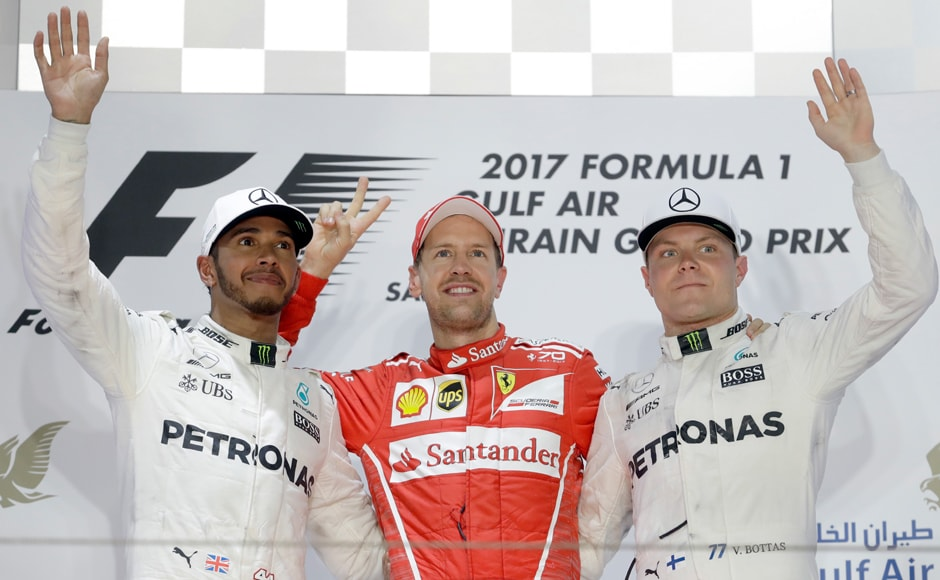 Ferrari driver Sebastian Vettel of Germany, center, celebrates after winning the Bahrain Formula One Grand Prix, with second placed Mercedes driver Lewis Hamilton of Britain, left and Mercedes driver Valtteri Bottas of Finland, right. AP