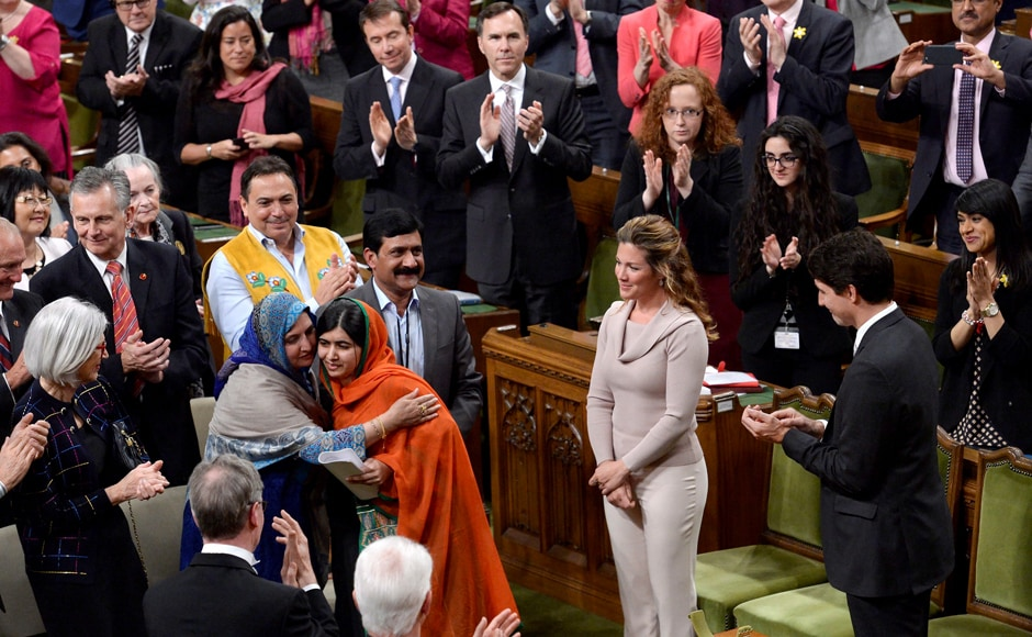 Pakistani activist and Nobel Peace Prize winner Malala Yousafzai, center, is hugged by her mother, Tor Pekai Yousafzai, as she's paid tribute in the House of Commons on Parliament Hill in Ottawa on Wednesday. AP