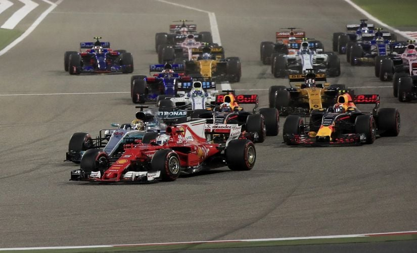 Ferrari driver Sebastian Vettel, foreground, overtakes Mercedes driver Lewis Hamilton, 2nd left, entering the first curve at the start of the Bahrain Grand Prix. AP