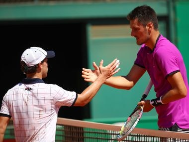 Bernard Tomic shakes hands at the net after his straight sets defeat by Diego Schwartzman. Getty