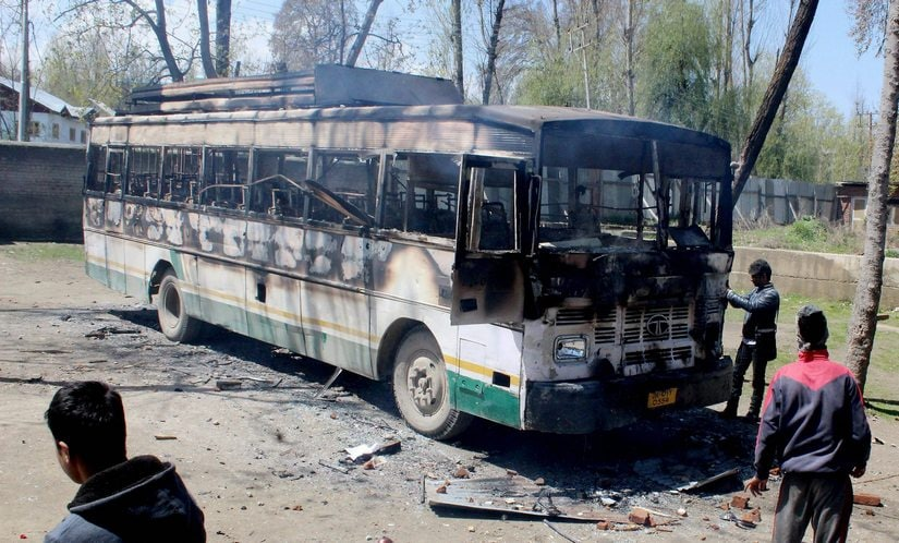Srinagar: A charred polling staff bus following an attack by a group of protesters at Nowgam during voting for Srinagar bypolls on Sunday. PTI Photo(PTI4_9_2017_000138B)