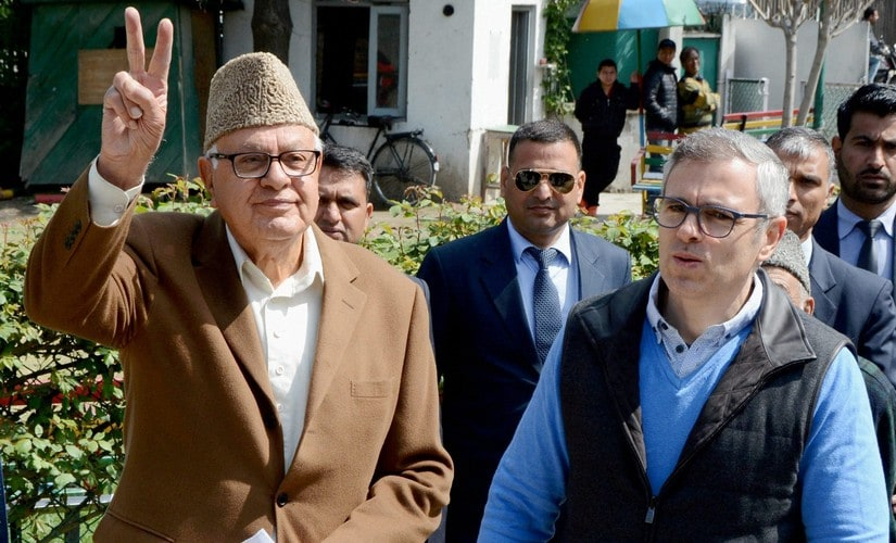 Srinagar: Former Union Minister and Congress-National Conference joint candidate Farooq Abdullah shows victory sign as his son and former Chief Minister Omar Abdullah looks on outside a polling station during voting for Srinagar parliamentary seat, on Sunday. PTI Photo (PTI4_9_2017_000085B)