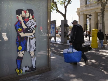 "A graffiti depicting Lionel Messi kissing Cristiano Ronaldo by street artist Salva ""Tvboy"" in Barcelona. AFP"
