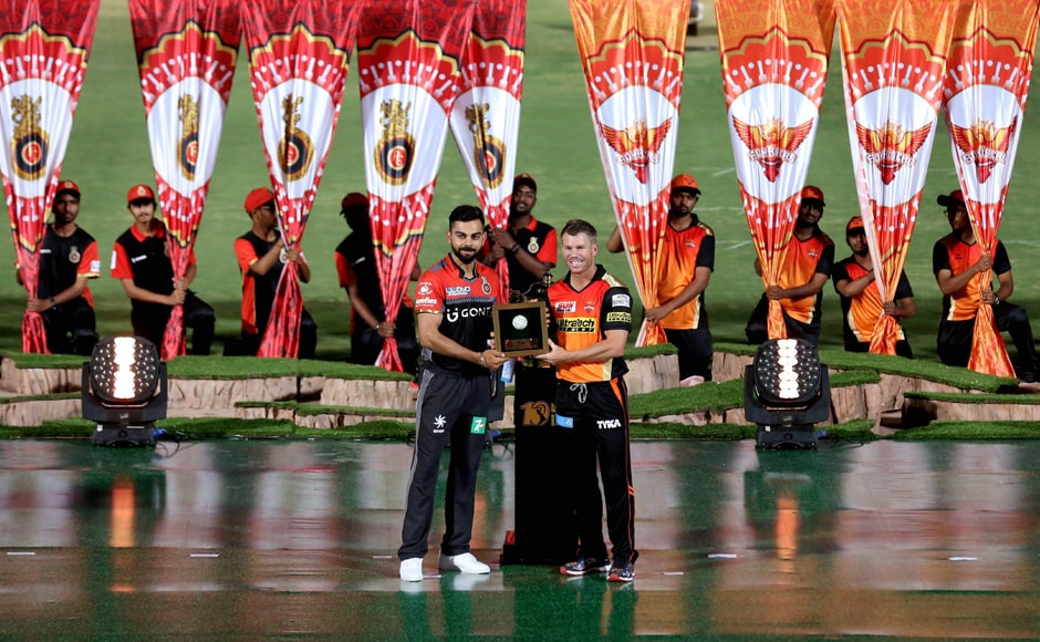 Sunrisers Hyderabad captain David Warner presents Virat Kohli, his counterpart in the Royal Challengers Bangalore, with a memento during the opening ceremony. PTI/Sportzpics