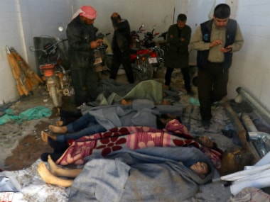 Men stand near dead bodies, after what rescue workers described as a suspected gas attack in the town of Khan Sheikhoun in rebel-held Idlib, Syria April 4
