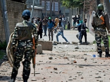 Youths throw stones on Security forces during clashes in Srinagar on Sunday. PTI