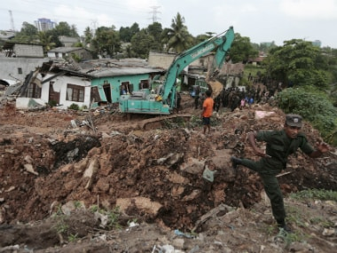 Sri Lankan army soldiers and rescue workers stand near buried houses in a collapse of a garbage dump in Meetotamulla, on the outskirts of Colombo, Sri Lanka, Saturday, April 15, 2017.