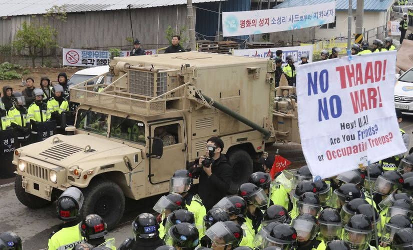 US military vehicle moves past banners opposing a plan to deploy advanced US missile defense system THAAD as South Korean police officers stand guard in Seongju in South Korea on Wednesday. AP