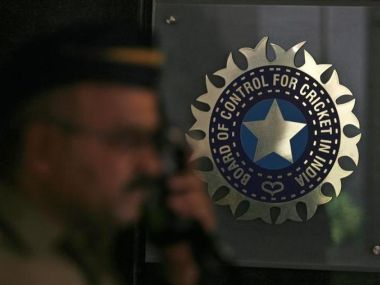 A policeman walks past a logo of the Board of Control for Cricket in India (BCCI). Reuters