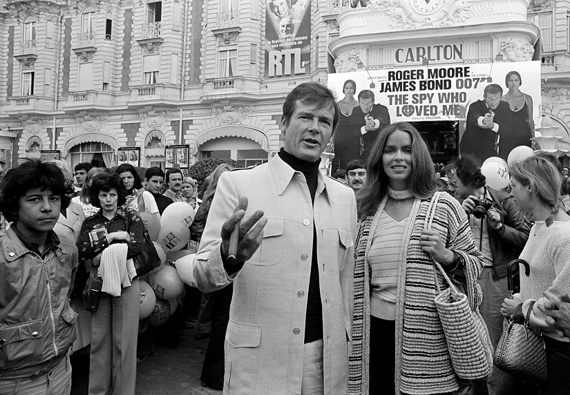 """FILE - In this May 20, 1977 file photo, actor Roger Moore, alias British secret agent James Bond, is accompanied by co-star Barbara Bach as they arrive for the screening of their latest 007 feature, """"The Spy Who Loved Me,"""" during the Cannes Film Festival at the French Riviera. Moore, played Bond in seven films, more than any other actor. (AP Photo, File)"""