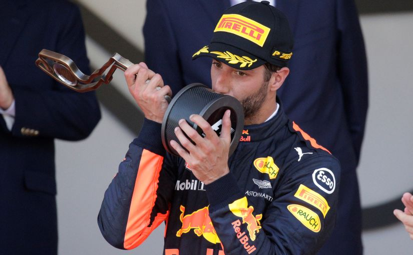 Red Bull's Daniel Ricciardo celebrates third place on the podium with the trophy. Reuters