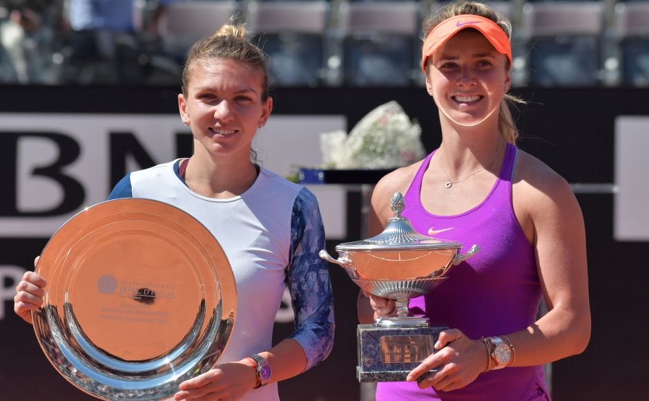 Elina Svitolina (R) of Ukraine poses with the trophy after winning the WTA Tennis Open final against Simona Halep (L) of Romania, on May 21, 2017 at the Foro Italico in Rome. Ukraine's Elina Svitolina stunned Romanian favourite Simona Halep 4-6, 7-5, 6-1 to win the WTA event at the Rome Masters today. / AFP PHOTO / Tiziana FABI