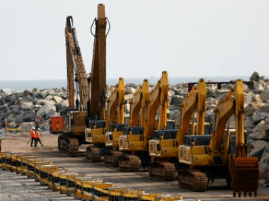 """People walk near excavators in line as they stop work at the construction site of Chinese investment """"Colombo Port City"""" in Colombo, Sri Lanka. (Representative image). Reuters"""