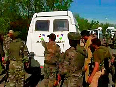 Security forces personnel inspect the site after suspected militants killed five policemen and two security guards while looting a cash van. PTI