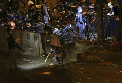 Police officers inspect the site where the bombing occurred. AP