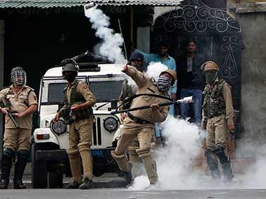 An Indian policeman throws a tear gas shell at Kashmiri protesters in Srinagar, Kashmir. AP