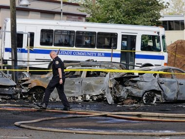 A police officer walks near the site of a deadly small plane crash near Teterboro Airport in Carlstadt, NJ, just west of New York City, Monday, May 15, 2017. Police said a Learjet 35 crashed into a building near the airport sparking a fire that sent thick, black smoke spewing into the air. AP