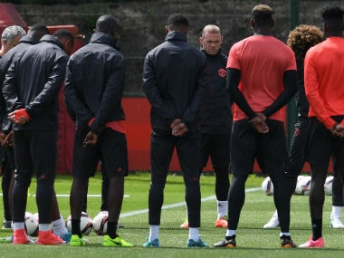 Manchester United's English striker Wayne Rooney (4R) stands with teammates as they observe a minute's silence for the victims of yesterday's terror attack at the Ariana Grande concert at the Manchester Arena last night, during a team training session at the club's training complex near Carrington. AFP