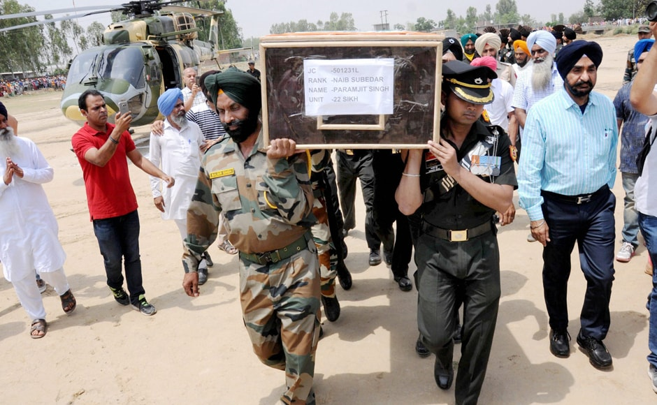 Army personnel carrying the mortal remais of late Naib Subedar Paramjit Singh at his village Vain Poin, some 40kms from Amritsar on Tuesday. The two soldiers were a part of a joint patrol team inspecting the border area to check the veracity of an intelligence report that landmines had been planted there by Pakistani troops. However, reports suggest that this could have been a death trap meant to cause damage to the frontal posts of the army in the region. PTI
