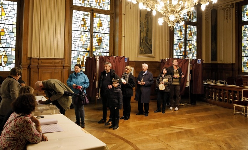 People line up to vote in the French presidential election at a polling station in Paris, France. AP