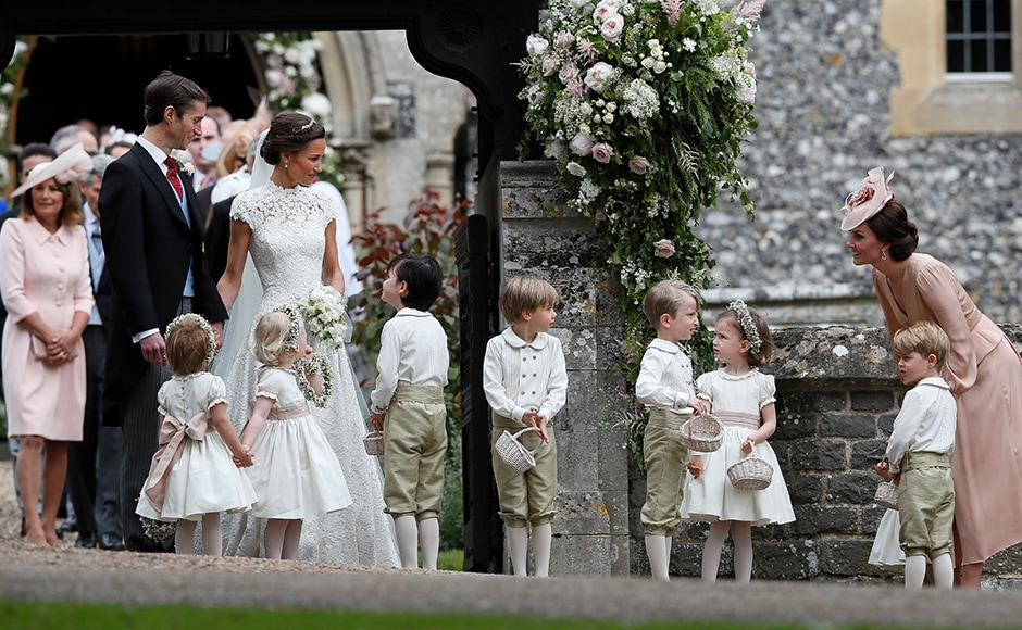 Kate, Duchess of Cambridge, right, stands with her son Prince George as she looks across at Pippa Middleton and James Matthews after their wedding at St Mark's Church in Englefield, England Saturday, May 20, 2017. Middleton, the sister of Kate, Duchess of Cambridge married hedge fund manager James Matthews in a ceremony Saturday where her niece and nephew Prince George and Princess Charlotte was in the wedding party, along with sister Kate and princes Harry and William. AP