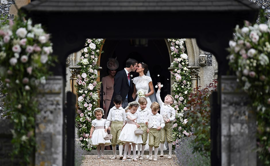 Pippa Middleton (centre R) kisses her new husband James Matthews, following their wedding ceremony at St Mark's Church in Englefield, west of London, on May 20, 2017, as the bridesmaids, including Britain's princess Charlotte (L) and pageboys, including Britain's prince George (2R), walk ahead. After turning heads at her sister Kate's wedding to Prince William, Pippa Middleton graduated from bridesmaid to bride on Saturday at a star-studded wedding in an English country church. The 33-year-old married financier James Matthews, 41, at a ceremony attended by the royal couple and tennis star Roger Federer, wearing a couture dress by British designer Giles Deacon. AP