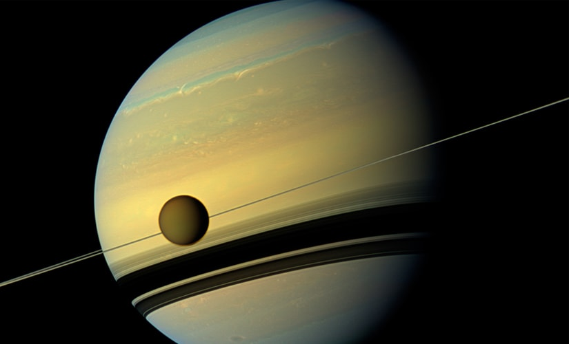 Titan, Saturn's largest moon appears before the planet as it undergoes seasonal changes in this natural color view from NASA's Cassini spacecraft in this handout released by NASA August 29, 2012. Reuters